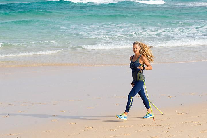 jill cooper cammina con legging begood sulla spiaggia